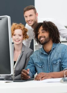 28756846 - happy african american man at work smiling as he sits with his colleagues in the studio at a computer creating a new innovation or design