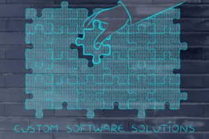 56146104 - custom software solutions: hand inserting missing piece of jigsaw puzzle with lines of binary code to fill a gap, metaphor illustration about software development and fixing bugs