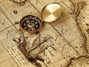 a compass lies on an age-old map