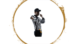 Picture of a referee holding a whistle to his mouth while pointing directly at the viewer