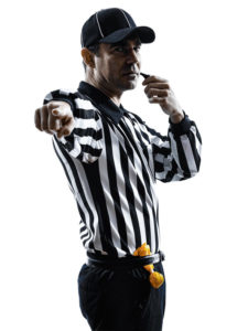 Picture of a referee holding a whistle to his mouth while pointing directly toward the person viewing the picture
