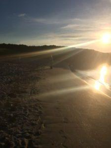 Woman on beach at sunrise