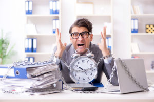 Man chained to clock very frustrated and overworked