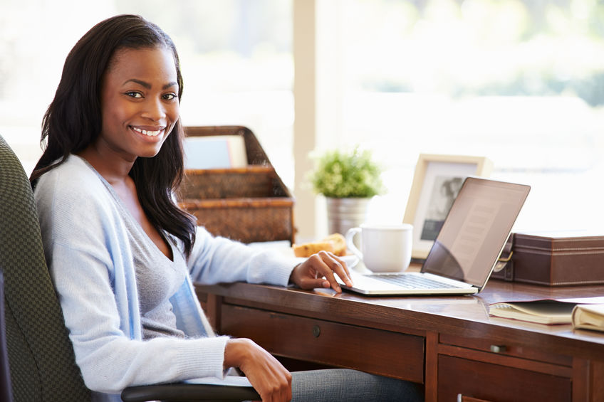 Woman sitting at desk with computer, smiling