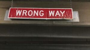 Wrong Way sign hanging from a parking garage ceiling.